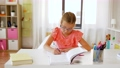 student girl with book writing to notebook at home 57625099