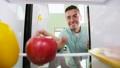 man taking apple from fridge at home kitchen 57625101