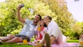 family having picnic and taking selfie at park 57625112