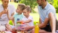 happy family eating fruits on picnic at park 57625115
