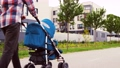 father with baby in stroller walking along city 57625637
