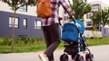 father with baby in stroller walking along city 57625641