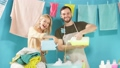 Crazy funny couple pouring different detergents in the bowl 57783620