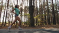 Sports girl runs along the road in a pine forest 57785279