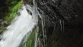 A stream of water of a waterfall is washed by a stone 57785332