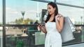 Stylish female model enjoying shopping using smartphone walking outdoor steadicam establish shot 57989335