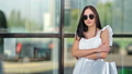 Fashionable smiling young woman in trendy sunglasses posing with shopping bag at window background 57989447