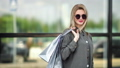 Portrait casual smiling blonde woman in stylish sunglasses posing with shopping bag 57989843