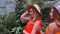 Portrait of girls with blonde hair in hats posing in botanic garden 58088935