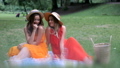 Sisters in dresses looking at each other having picnic in park 58088949