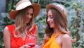 Portrait of girls in hats holding glasses of wine in botanical garden 58088973