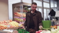 Young man emotionally choosing fresh cucumbers in supermarket 58288256