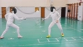 Two young women in protective helmets having an active fencing training in the school gym - making 58290339