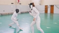 Two young women in full protection having an active fencing training in the school gym - making 58290345
