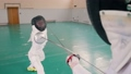Two young women in white protective suits having a fencing training in the gym 58290385