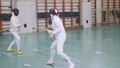 Two young women having an active fencing training in the school gym 58291436