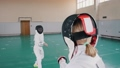 Two young women in white protective suits having a fencing training - one woman attack and another 58291459