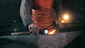 Blacksmith is using hammer to forge metal 58320396