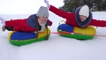 Children's Christmas holidays outdoors. Happy children have fun riding snow saucer and laugh on 58360206