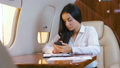 Beautiful businesswoman working with paper documents while aircraft flying. Business lady traveling 58418394