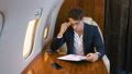 Businessman works with documents while flying in a personal jet plane. Business Class. 58418399