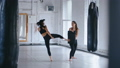 Athletic Woman Trains Her Kicks on a Punching Bag that Her Partner Holds. Training of Taekwondo or 58418405