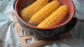 Setting a pot with steamed corn cobs on a table 58506548