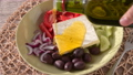 Pouring olive oil onto Greek salad with feta cheese, Kalamata olives, cucumber, tomato, red onion 58506553
