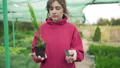 Beautiful young woman florist - business owner is holding a growing green plant and a dry tree 58716804