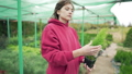 Young woman florist - business owner with a plant in her hands. Evergreen seedling in a small pot 58716818