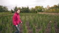 Success. Woman florist in a field next to conifers rejoices in a large order. Happy female 58716828