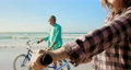 Active senior Caucasian couple standing with bicycle on the beach 4k 59438331