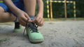 Boy footballer tying shoelaces, special orthopedic 59857725