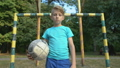 Serious boy with football looking into camera at 59857728