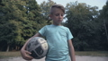 Lonely upset boy holding football at pitch, lack 59857730