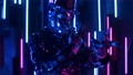 A man dances in neon light in a glass suit. Shiny sparkling silver suit, and blue purple neon light 60075718