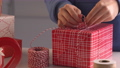 A young woman in blue is wrapping, packaging Christmas gift for kids children by beautiful, red, white wrapper with glittering light, lifestyle. 60268213