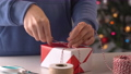 A young woman in blue is wrapping, packaging Christmas gift for kids children by beautiful, red, white wrapper with glittering light, lifestyle. 60268217