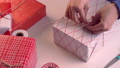 A young woman in blue is wrapping, packaging beautiful gift box for holiday with wrapper and rope to tie a bow-knot, lifestyle, close up. 60268224