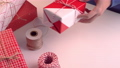 A young woman in blue is wrapping, packaging beautiful gift box for holiday with wrapper and rope to tie a bow-knot, lifestyle, close up. 60268226