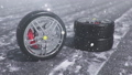 Winter tires on a background of snowstorm, snowfall and slippery winter road. Winter tires concept. Wheel replacement. Road safety concept. FullHD 3d animation with falling snow 60441096