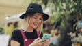 Young Blond Caucasian Girl Wearing a Black Hat Using her Smartphone Listening to a Voice Messege 60708022