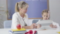 Portrait of adult Caucasian woman and little schoolgirl sitting at the table with tablet. Smart tutor teaching schoolgirl at home. Education, private teaching. Camera moving from right to left. 60839884