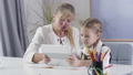 Portrait of middle aged Caucasian woman and little schoolgirl sitting at the table with tablet. Tutor teaching schoolgirl at home. Education, private teaching. Camera moving from left to right. 60839887
