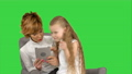 Young mother and her daughter sit together and look at the tablet on a Green Screen, Chroma Key 60960484