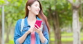 asian woman use smartphone outdoor while walking in the park 61239650