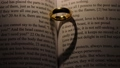 Golden wedding ring on bible book 61292657