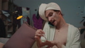 Close up of transgender man with towel on head painting nails and talking on phone. Young trans man 61705074