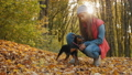 A girl petting her dog in the autumn park 61868250