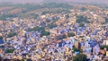 Jodhpur the Blue City aerial view. Blue painted houses and birds flying in the morning above brahmin houses, view from Mehrangarh Fort, Rajasthan, India. Camera zoom in 62467955